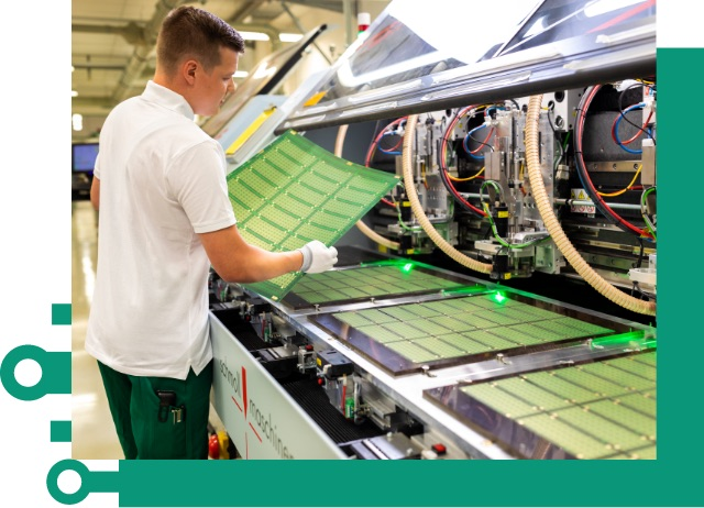 Image of a young employee at a printed circuit board production machine