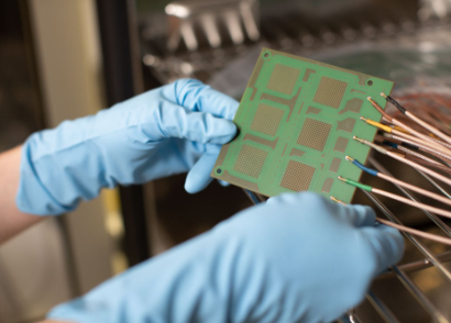 KSG employee holds printed circuit board with test structure in both hands