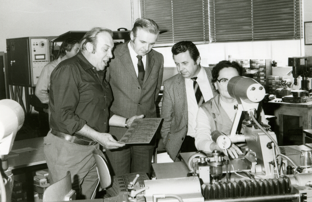 Employees looking at the first printed circuit board produced in Gars